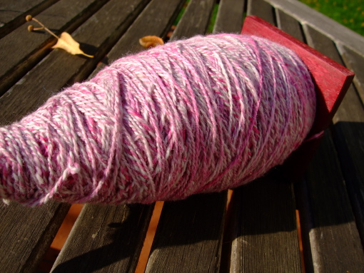 130 grams of fingering weight 2-ply yarn on a spindle.