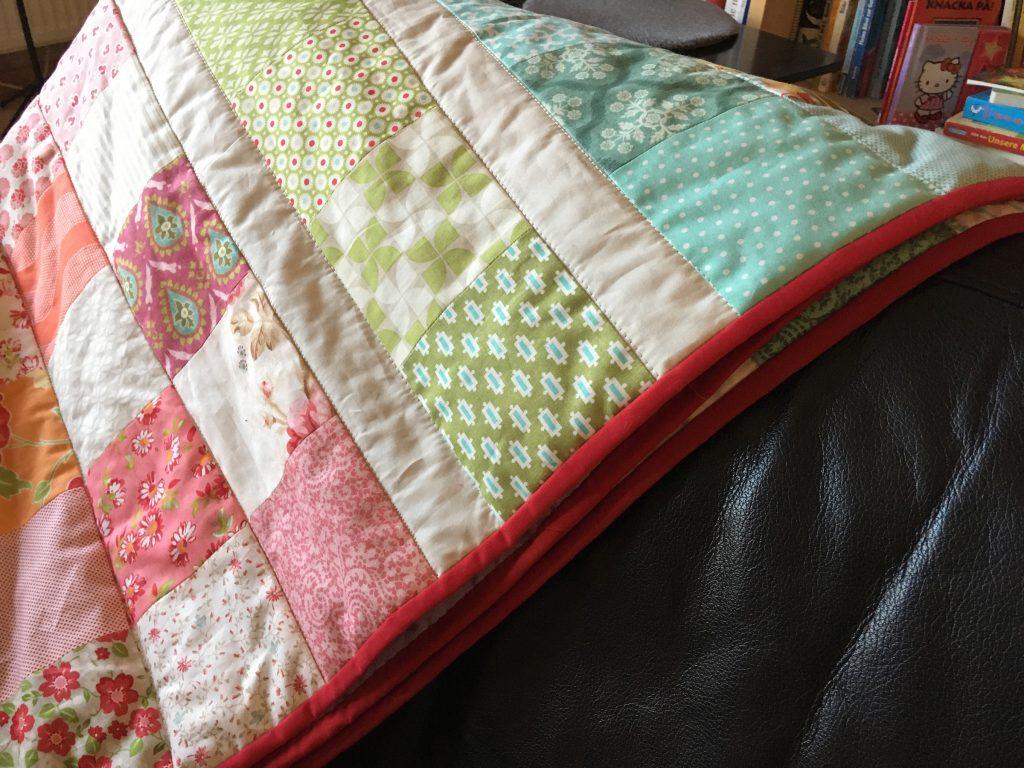Charm Pack Quilt mit Jelly Roll Stripes als Zwischentrenner
